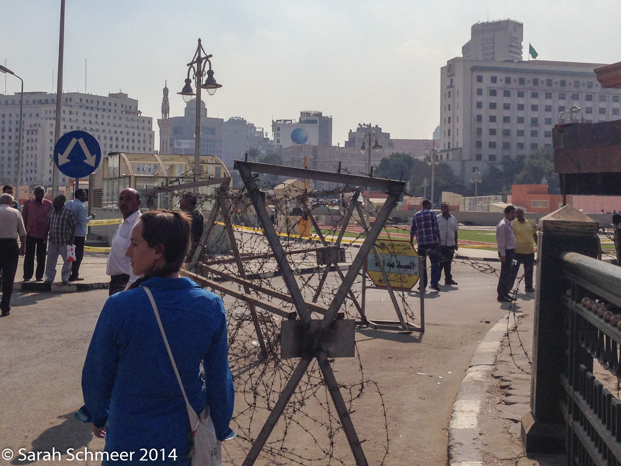 Negotiating the tangle of people, cars and barbed wire in front of the museum