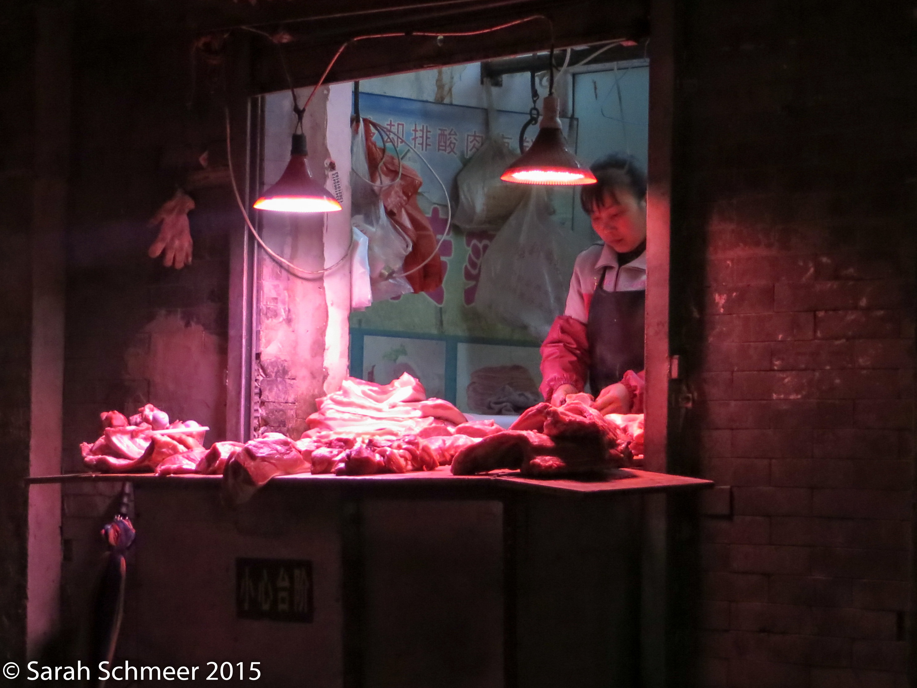 The butcher keeps an eye on cuts of beef, pig and mutton.